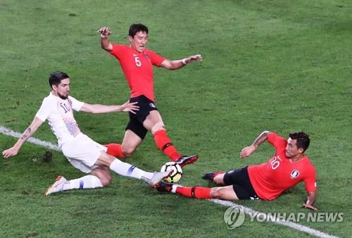 Jung Woo-young (C) and Jang Hyun-soo of South Korea (R) battle Diego Valdes of Chile for the ball during their friendly football match at Suwon World Cup Stadium in Suwon, 45 kilometers south of Seoul, on Sept. 11, 2018. (Yonhap)