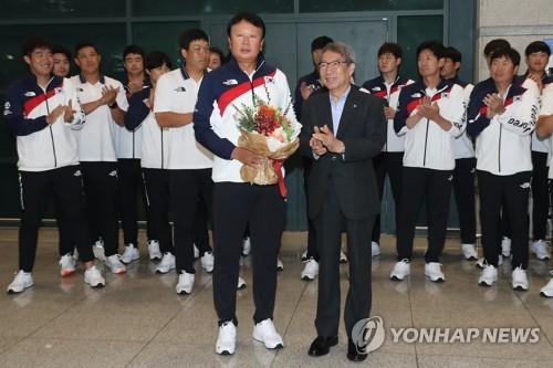 In this file photo from Sept. 3, 2018, Sun Dong-yol (L), manager of the South Korean national baseball team, poses for photos next to Chung Un-chan, commissioner of the Korea Baseball Organization, at Incheon International Airport, west of Seoul, after winning the gold medal at the Jakarta-Palembang Asian Games. Sun's players in the back didn't wear their gold medals for the occasion. (Yonhap)