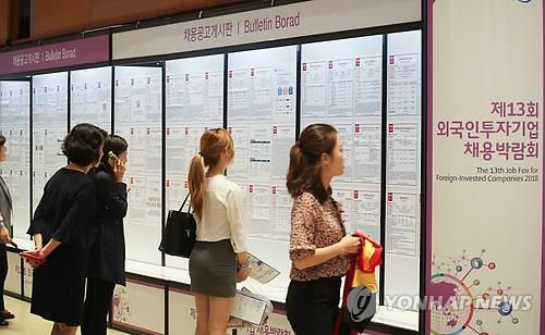 Jobseekers look at recruitment notices during a job fair of foreign-invested companies at a convention center in Seoul on June 14, 2018, in this file photo.