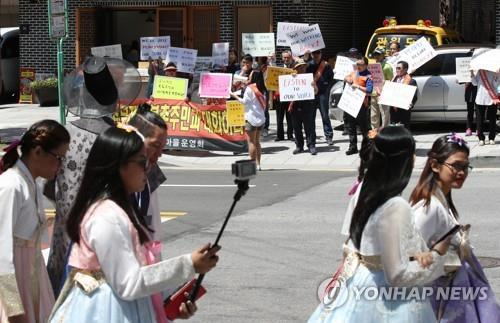 "In this file photo taken on May 19, 2018, tourists wearing traditional Korean attire, or ""hanbok,"" pass by a group protesting against tourists visiting Bukchon Hanok Village in central Seoul. The residents from the traditional village argue that the overwhelming number of visitors disrupts their lives and leaves tons of trash in the neighborhood. (Yonhap)"