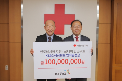 In this photo provided by KT&G Corp., Lee Sang-hak (R), the company's chief of sustainability management team, poses for a photo with Park Kyung-seo, president of the Korean Red Cross, during a ceremony in Seoul on Oct. 4, 2018, to donate funds to earthquake-hit Indonesia. (Yonhap)
