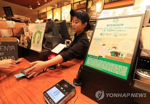 A cashier at a Starbucks coffee shop in Seoul receives credit card from a customer on July 16, 2018. (Yonhap)