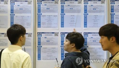 This photo, taken Oct. 4, 2018, shows job seekers looking at recruitment notices at a job fair in Seoul. (Yonhap)