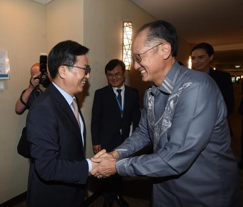 This photo provided by the finance ministry shows South Korean Finance Minister Kim Dong-yeon (R) shaking hands with World Bank President Jim Yong Kim during a meeting on the Indonesian resort island of Bali on Oct. 13, 2018. (Yonhap)