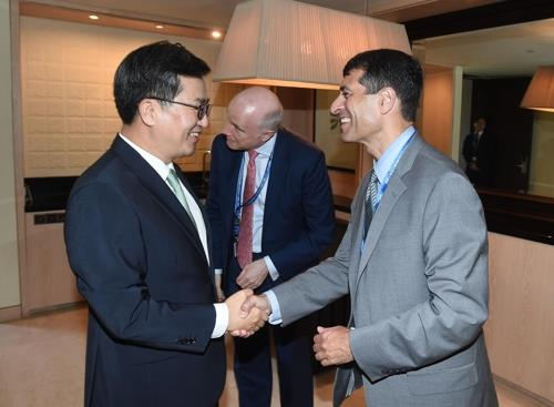 Finance Minister Kim Dong-yeon (L) shakes hands with Stephen Schwartz, head of Asia Pacific sovereign ratings in Bali, Indonesia, on Oct. 12, 2018. (Yonhap)