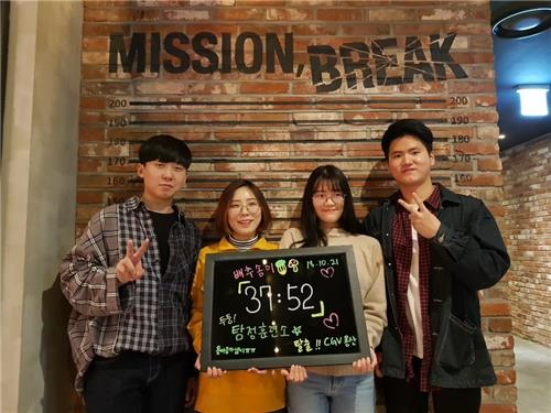 In this photo, taken Oct. 21, 2018, (from left) Chu Seung-yeop (22), Lee Ho-young (20), Song Eun-bi (21), and Bae Yong-bi (21) pose for a photo proving they finished an escape room about 20 minutes earlier than the given one-hour time limit at Yongsan CGV, central Seoul. (Yonhap)