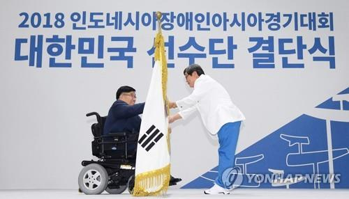 This file pool photo taken on Sept. 19, 2018, shows Korea Paralympic Committee (KPC) President Lee Myung-ho handing the national flag to Jun Min-sik, South Korea's chef de mission for the Asian Para Games in Indonesia, at the national team launching ceremony in Icheon, Gyeonggi Province. (Yonhap)