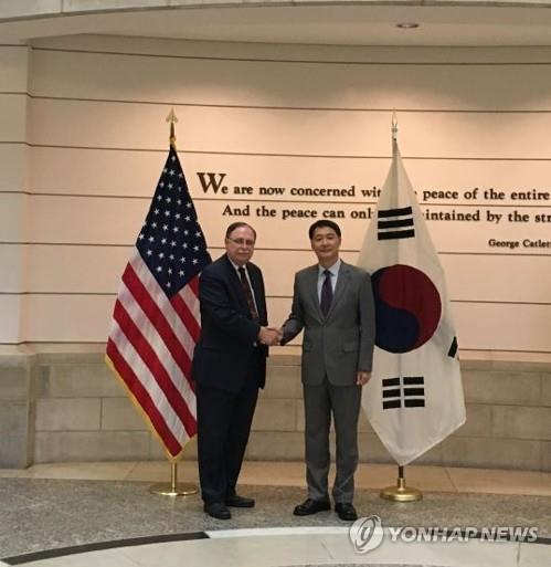 Chang Won-sam (R), South Korea's top negotiator in defense cost-sharing talks with the United States, shakes hands with his counterpart, Timothy Betts, in a file photo provided by Seoul's foreign ministry. (Yonhap)