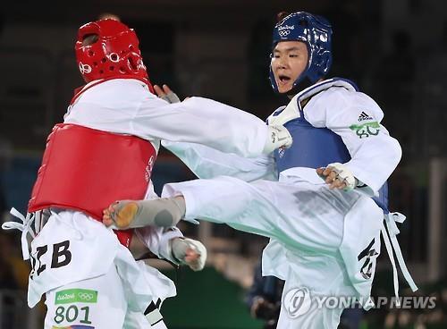 Attaque pour le bronze. Cha Dong-min frappe le tronc de son adversaire, l'Ouzbek Dmitriy Shokin, lors du combat de la troisième place de taekwondo des plus de 80kg hommes des Jeux olympiques de Rio de Janeiro, le 20 août 2016 (heure locale)