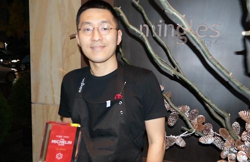 Le chef propriétaire du restaurant coréen contemporain Mingles pose devant l'entrée de son établissement après une interview avec Yonhap le 18 novembre 2016