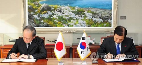 Le ministre de la Défense Han Min-koo (à droite) et l'ambassadeur du Japon en Corée du Sud Yasumasa Nagamine signent le GSOMIA au ministère de la Défense à Séoul (Photo d'archives Yonhap)