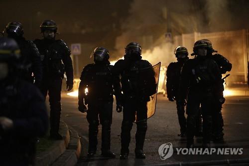 Des policiers antiémeute regardent un incendie provoqué lors du rassemblement de manifestants en contestation de l'affaire Théo, le 11 février 2017 (heure de Paris) (AFP=Yonhap)
