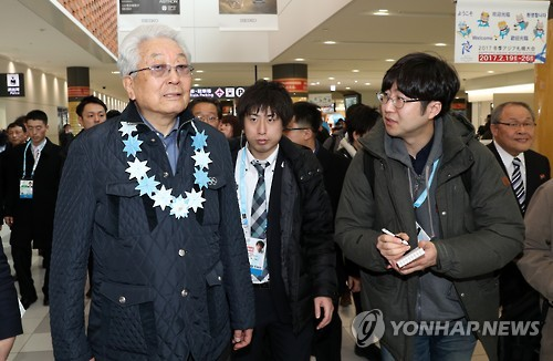 Un journaliste de Yonhap (à droite) pose une question à Chang Ung (à gauche), membre nord-coréen du Comité international olympique (CIO), lors de l'arrivée de l'équipe nord-coréenne à Saporro pour les Jeux asiatiques d'hiver, le 17 février 2017.