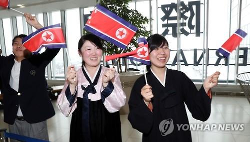 Des membres de l'Association générale des résidents coréens au Japon accueillent les athlètes de l'équipe nord-coréenne à Saporro au Japon en agitant le drapeau national de la Corée du Nord, le 17 février 2017.