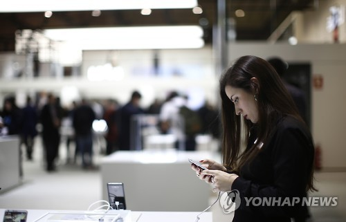 Une femme regarde le G6 de LG au Mobile World Congress 2017 à Barcelone (AP=Yonhap)