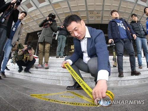 Un personnel du Parquet marque la limite pour les photojournalistes de la présidente Park Geun-hye lors de sa comparution devant le Parquet prévue le 21 mars 2017 à 9h30 du matin