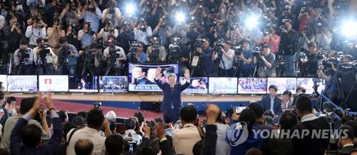 Le président élu Moon Jae-in salue les membres de son parti au Parlement juste après la fermeture des bureaux de vote, le 9 mai 2017.