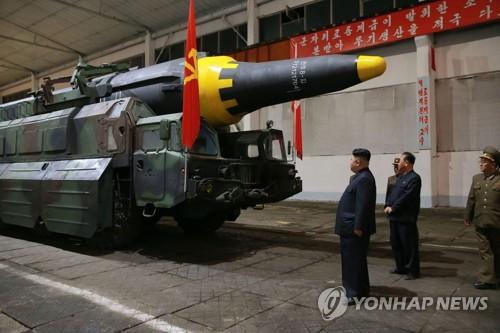 A la veille du tir de missile balistique Hwasong-12 (appellation nord-coréenne), le jeune leader du régime nord-coréen, Kim Jong-un, regarde un tracteur-érecteur-lanceur. (KCNA=Yonhap, Utilisation en Corée du Sud uniquement et redistribution interdite)