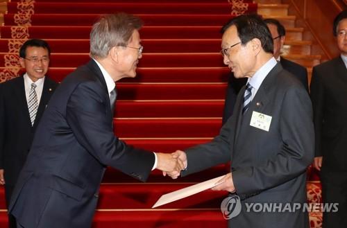 Le président Moon Jae-in (à gauche) serre la main de l'envoyé spécial en Chine Lee Hae-chan après lui avoir remis la lettre adressée au président chinois Xi Jinping, le 16 mai 2017 au palais présidentiel.