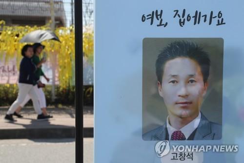 Une pancarte montrant une photo d'identité du professeur Ko Chang-seok du lycée Danwon, dans le nouveau port de Mokpo où l'épave du Sewol a été mise en cale sèche.