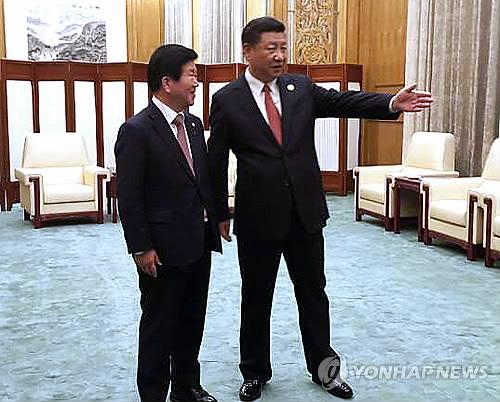 Le député Park Byeong-seug (à gauche) du parti au pouvoir, le Parti démocrate de Corée, qui dirige la délégation sud-coréenne du forum «Une ceinture et une route» pour la coopération internationale, rencontre le dimanche 14 mai 2017 le président chinois Xi Jinping. © Secrétariat du député Park Byeong-seug. (Photo d'archives)