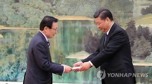 L'émissaire spécial Lee Hae-chan (à gauche) du président Moon Jae-in remet la lettre de Moon au président Xi Jin-ping ce vendredi 19 mai 2017 à Pékin.