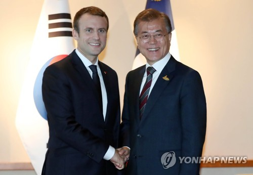 Le président français Emmanuel Macron (à gauche) et le président Moon Jae-in se saluent avant d'entamer leur première rencontre depuis leur investiture, le 10 mai dernier pour Moon et le 14 mai pour Macron. Ce sommet bilatéral en marge du sommet du G20 en Allemagne s'est déroulé à l'hôtel Hyatt à Hambourg dans l'après-midi du 8 juillet 2017 (heure locale).