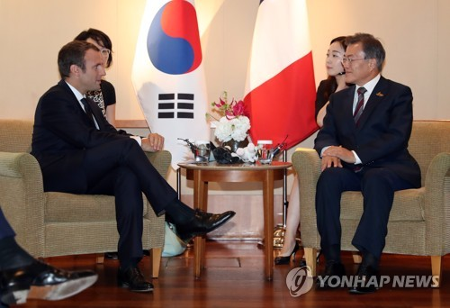 Le président Moon Jae-in (à droite) et son homologue français Emmanuel Macron discutent lors du sommet bilatéral en marge du sommet du G20 à Hambourg en Allemagne, à l'hôtel Hyatt dans l'après-midi du 8 juillet 2017.