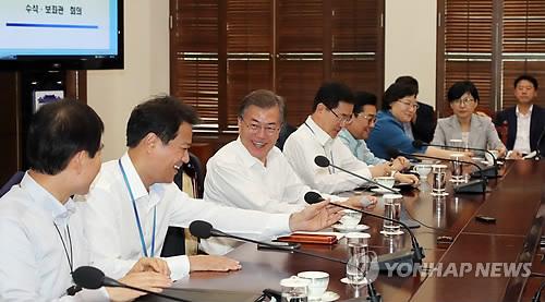 Le président Moon (troisième depuis la gauche) sourit lors d'une réunion du cabinet présidentiel, le 17 juillet 2017, à la Maison-Bleue.