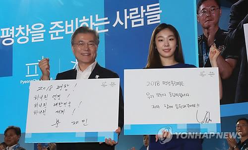 Le président Moon Jae-in et l'ancienne patineuse artistique Kim Yu-na posent pour une séance photos en portant des messages de soutien le lundi 24 juillet 2017 à l'Alpensia Ski Resort à PyeongChang, dans la province du Gangwon, lors d'un événement pour marquer les 200 jours avant le début des Jeux olympiques d'hiver de PyeongChang 2018.