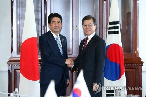 Le président Moon Jae-in et le Premier ministre japonais Shinzo Abe échangent une poignée de main avant leur sommet à Vladivostok en Russie.