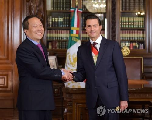 Le président mexicain Enrique Pena Nieto échange une poignée de main avec l'ambassadeur nord-coréen au Mexique Kim Hyong-gil en juin 2016. (EPA=Yonhap)