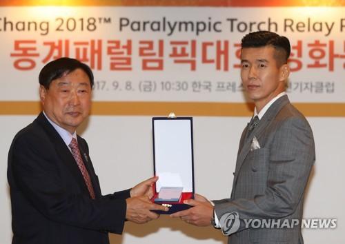 Le chef du POCOG Lee Hee-beom (à gauche) remet une plaque au chanteur sud-coréen Sean, nommé ambassadeur honoraire des Jeux paralympiques de PyeongChang 2018 ce vendredi 8 septembre 2017 à Séoul.