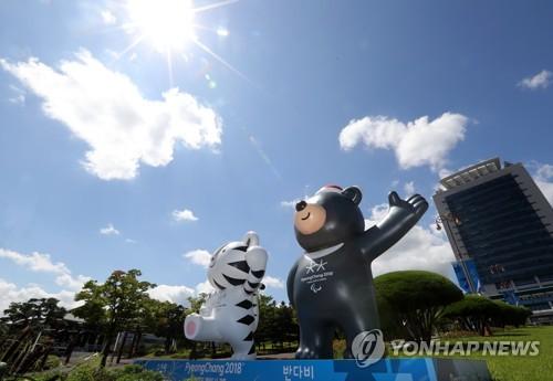 Les mascottes des Jeux olympiques d'hiver de PyeongChang 2018, Soohorang (à g.), tigre blanc, et Bandabi, ours noir d'Asie, devant la mairie de Gangneung, dans la province du Gangwon. (Photo d'archives Yonhap)