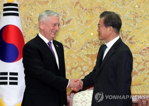 Le président Moon Jae-in échange une poignée de main avec le secrétaire à la Défense des Etats Unis James Mattis
