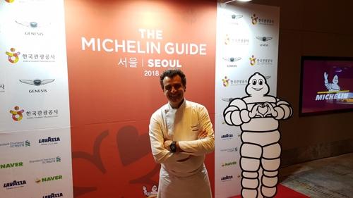 La star de la cuisine française Yannick Alléno pose à côté du Bonhomme Michelin, appelé aussi Bibendum, lors de la soirée «Art of Taste» pour la sortie du guide Michelin Séoul 2018, le mercredi 8 novembre 2017.