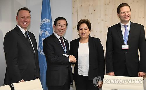 Le maire de Séoul, Park Won-soon serre la main de la secrétaire exécutive de la Convention-cadre des Nations unies sur les changements climatiques (CCNUCC), Patricia Espinosa, à Bonn, en Allemagne, le samedi 11 novembre 2017.