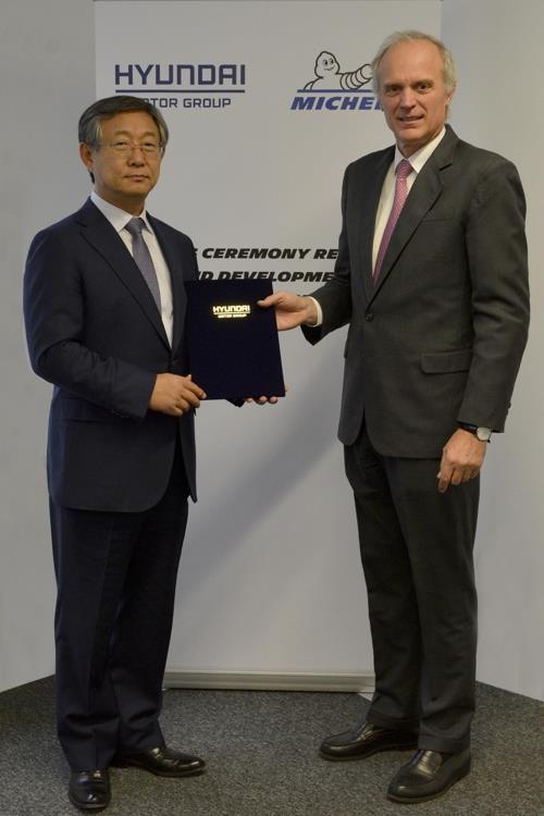 Cette photo fournie par Hyundai Motor Co. le 15 novembre 2017 montre Yang Woong-cheol (à g.), vice-président de Hyundai Motor, posant avec son homologue de la société Michelin, Florent Menegaux, après la signature d'un accord de partenariat au Centre de recherche et de développement de Michelin situé à Clermont-Ferrand, dans le centre de la France.