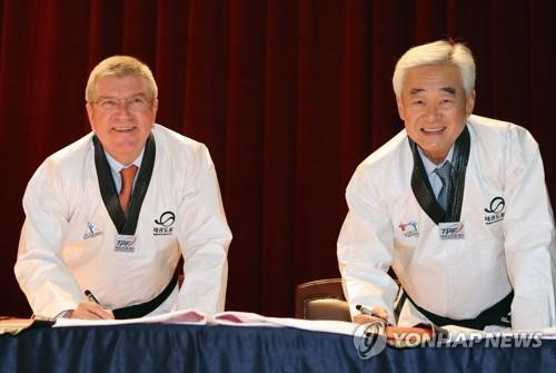 Sur cette photo d'archive prise le 30 juin 2017, le président de la Fédération mondiale de taekwondo (WT) Choue Chung-won (à d.) pose avec le président du Comité international olympique (CIO), Thomas Bach, au Taekwondo Park à Muju, dans la province du Jeolla du Nord.