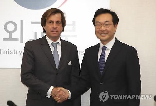 Poignée de main entre Lee Do-hoon (à d.), représentant spécial pour la paix sur la péninsule coréenne et les affaires de sécurité, et son homologue français Nicolas de Rivière lors d'une réunion à Séoul, le 5 décembre 2017, pour discuter de leur approche coordonnée du dossier nucléaire nord-coréen.