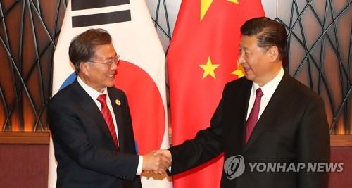 Le président Moon Jae-in et son homologue chinois Xi Jinping échangent une poignée de main le samedi 11 novembre 2017 à l'hôtel Crowne Plaza à Da Nang, au Vietnam, lors de leur sommet bilatéral.