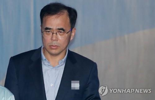 Kim Chong, ancien vice-ministre de la Culture, du Sport et du Tourisme, est escorté à la salle d'audience le 6 décembre 2017 pour entendre sa condamnation dans le sillage du scandale de trafic d'influence qui a mené à l'éviction de la présidente Park Geun-hye en mars.