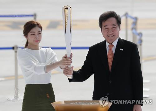 Sur cette photo d'archives prise le 1er novembre 2017, l'ancienne médaillée d'or olympique de patinage artistique Kim Yu-na (à g.) et le Premier ministre sud-coréen Lee Nak-yon tiennent le flambeau des Jeux olympiques d'hiver de PyeongChang 2018 lors de la cérémonie d'arrivée de la flamme olympique à l'aéroport international d'Incheon.