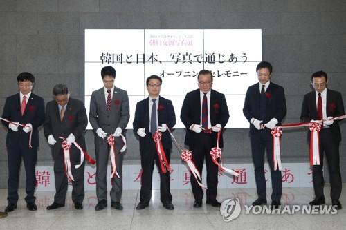 Des officiels sud-coréens et japonais coupent le ruban lors de la cérémonie d'ouverture de l'exposition de photos coorganisée par l'agence de presse Yonhap, le Musée national d'histoire contemporaine de Corée et le Centre culturel coréen à Tokyo le 20 décembre 2017.