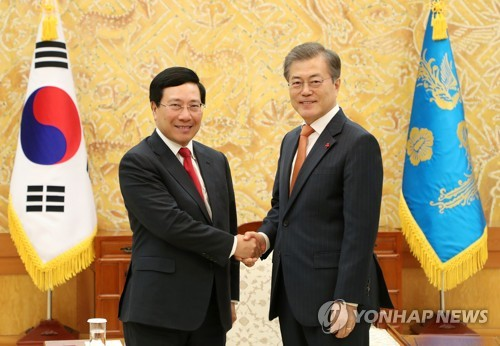 Le président Moon Jae-in (à droite) serre la main du vice-Premier ministre et ministre des Affaires étrangères vietnamien Pham Binh Minh au bureau présidentiel à Séoul ce jeudi 21 décembre 2017.