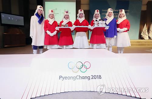 Des mannequins portant les costumes pour les cérémonies de remise des médailles aux Jeux olympiques d'hiver de PyeongChang 2018 posent pour une séance photos derrière un podium le mercredi 27 décembre 2017 lors d'une présentation devant la presse à Séoul.