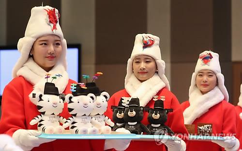Des mannequins en costume pour les cérémonies de remise des médailles aux Jeux olympiques d'hiver de PyeongChang 2018 portent des mascottes qui seront offertes aux médaillés durant l'événement sportif hivernal.