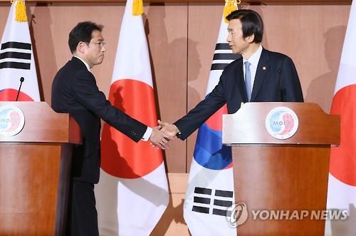 Cette photo datant du 28 décembre 2016 montre le ministre des Affaires étrangères Yun Byung-se de l'époque (à droite) et son homologue japonais Fumio Kishida échanger une poignée de main après avoir annoncé un accord pour résoudre la question des anciennes esclaves sexuelles.