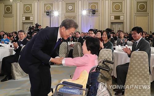 Le président Moon Jae-in serre les mains de Lee Hee-ah, une pianiste sud-coréenne qui n'a que quatre doigts, après un récital donné lors d'un déjeuner pour la nouvelle année à Cheong Wa Dae, le 2 janvier 2018.