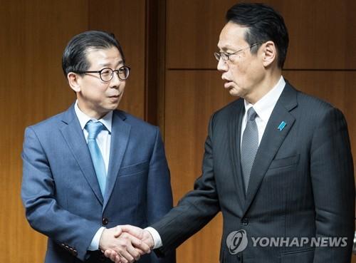Kim Yong-kil (à gauche) salue son homologue japonais Kenji Kanasugi ce lunid 8 janvier 2018 à Séoul.
